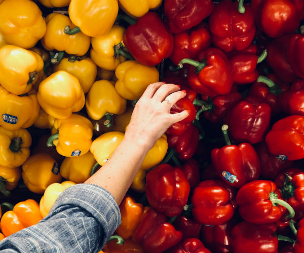 average grocery bill woman reaching for peppers