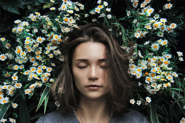 how to sleep better woman surrounded by flowers